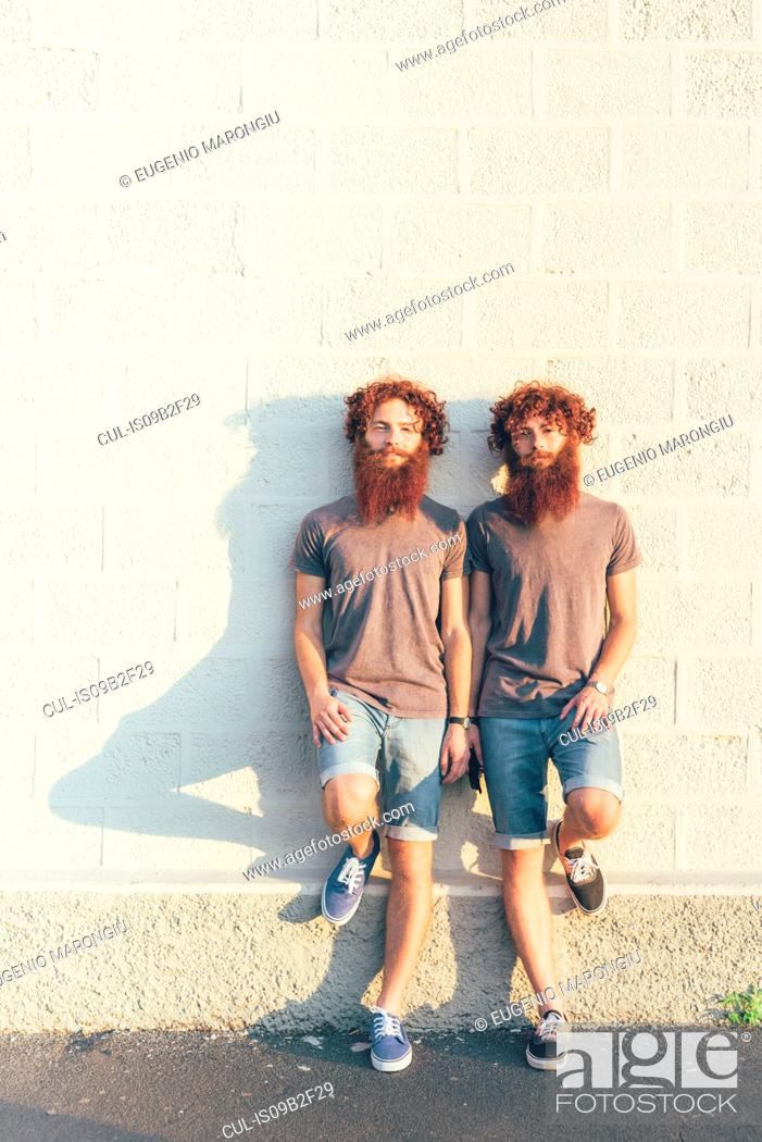 Stock Photo: Portrait of identical adult male twins with red hair and beards against white wall.
