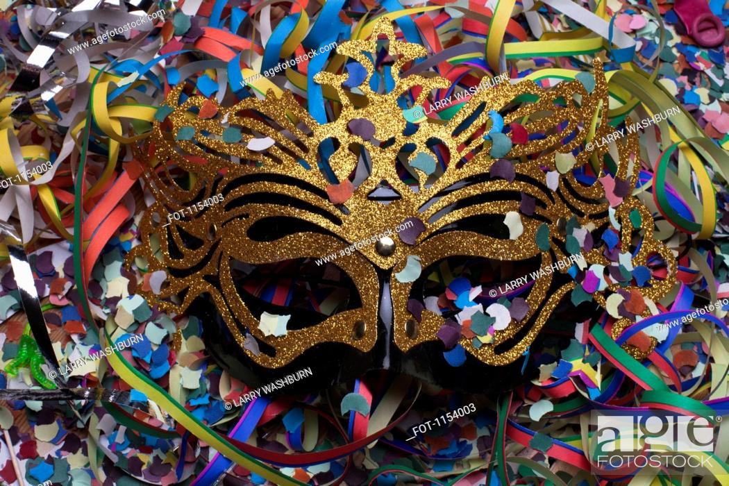Stock Photo: A masquerade mask nestled among confetti and streamers.