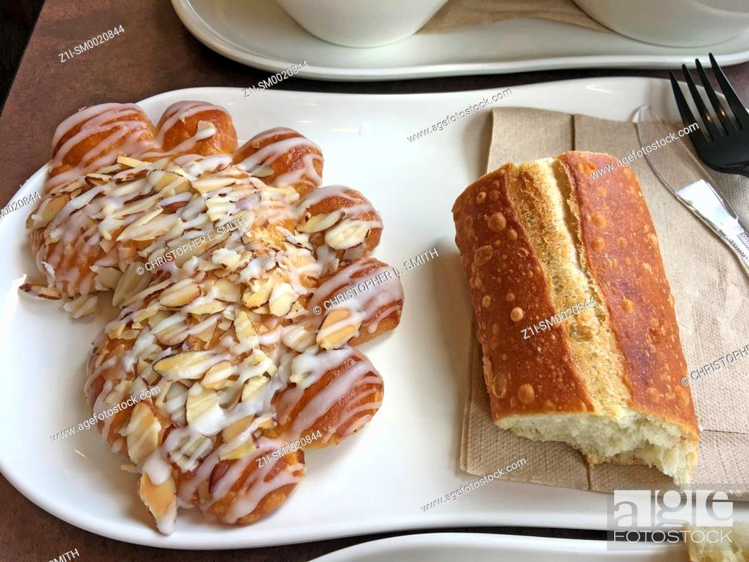 Stock Photo: Freshly baked bearclaw pastry and French bread on a white plate.
