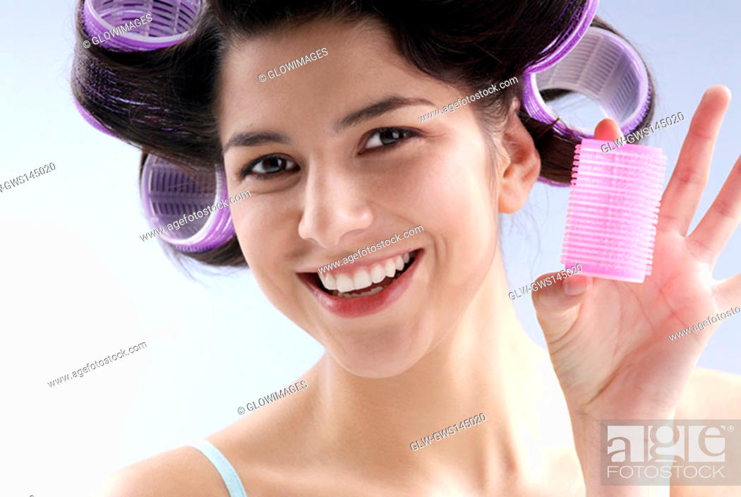 Stock Photo: Close-up of a young woman holding a hair curler.