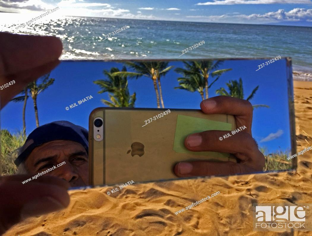 Stock Photo: A man combines the sea, the sand, and the trees in a selfie on the beach, Maui, Hawaii, USA.