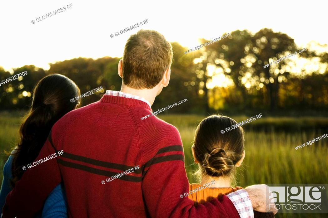 Stock Photo: Rear view of a mid adult couple standing with their daughter.