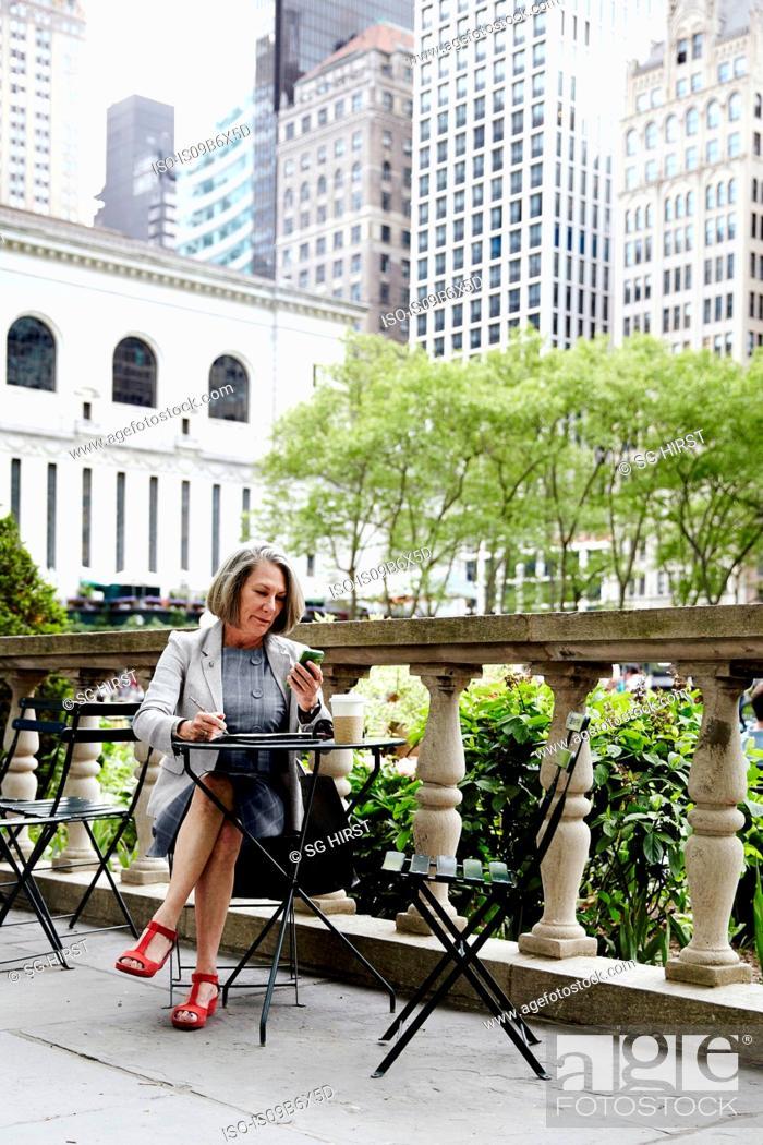 Stock Photo: Businesswoman working on balcony, New York, USA.