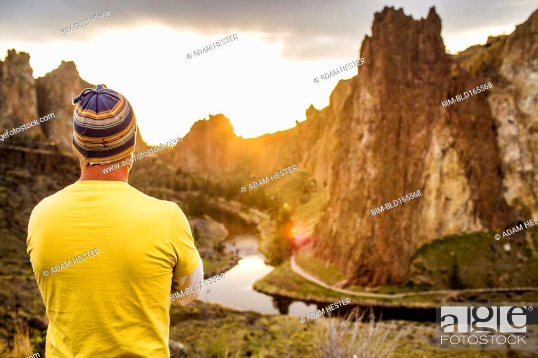 Stock Photo: Caucasian man admiring scenic desert landscape, Smith Rock State Park, Oregon, United States.