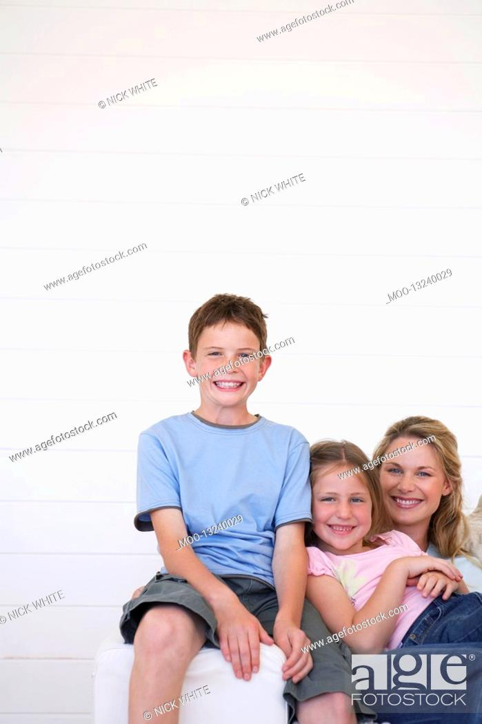 Stock Photo: Portrait of mother and children sitting on couch in weather boarded room.
