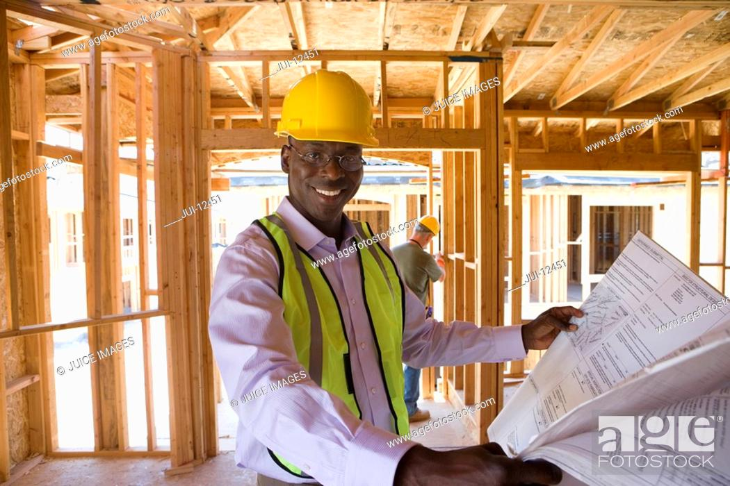 Stock Photo: Businessman in hardhat with blueprints in partially built house, smiling, portrait.