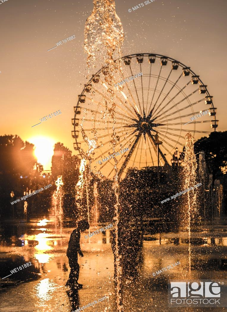 Stock Photo: Child Playing in the Water Fountain with Ferris Wheel in Background in Sunset in Nice, France.