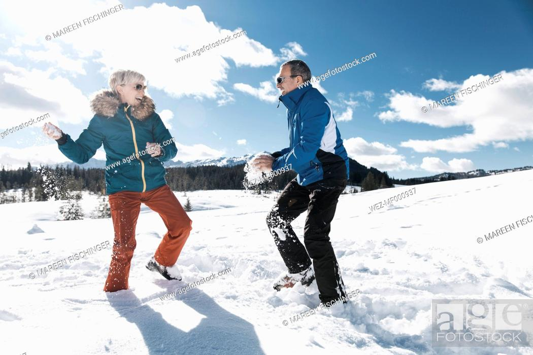 Stock Photo: Germany, Bavaria, Winklmoosalm, Mature couple having a snowball fight.