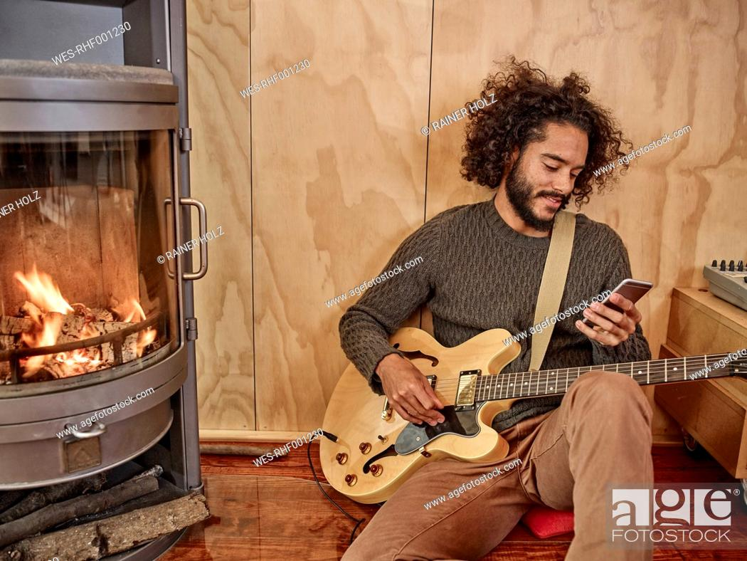 Imagen: Young man with electric guitar looking at cell phone.