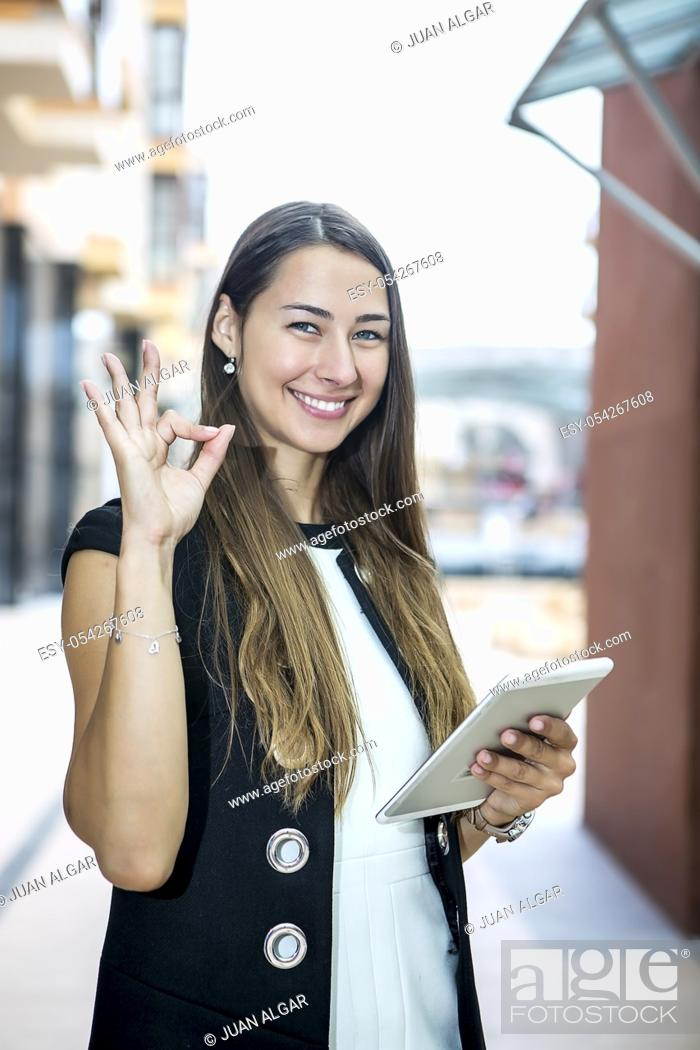 Stock Photo: Young smiling woman in elegant outfit holding table and showing OK gesture looking at camera.