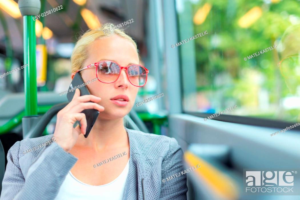 Stock Photo: Blonde caucasian business woman talking on cell phone, traveling by bus. Public transport and commuting to work.