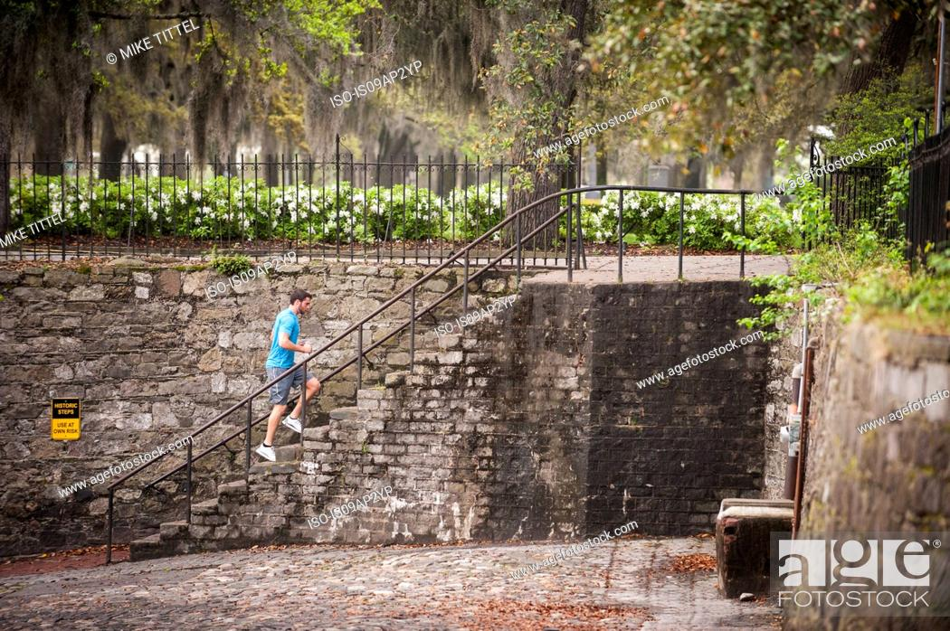 Stock Photo: Jogger along the river walk, Savannah, Georgia, USA.