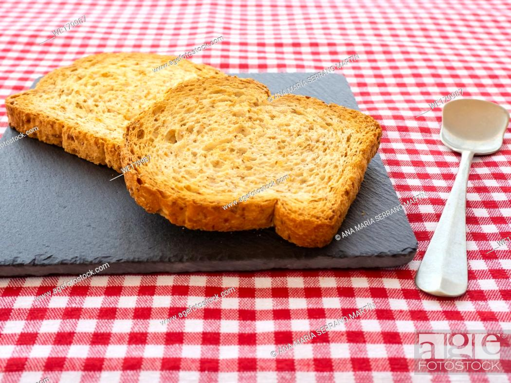 Stock Photo: Two slices of toast on a slate plate, one old spoon and tablecloth vintage style.