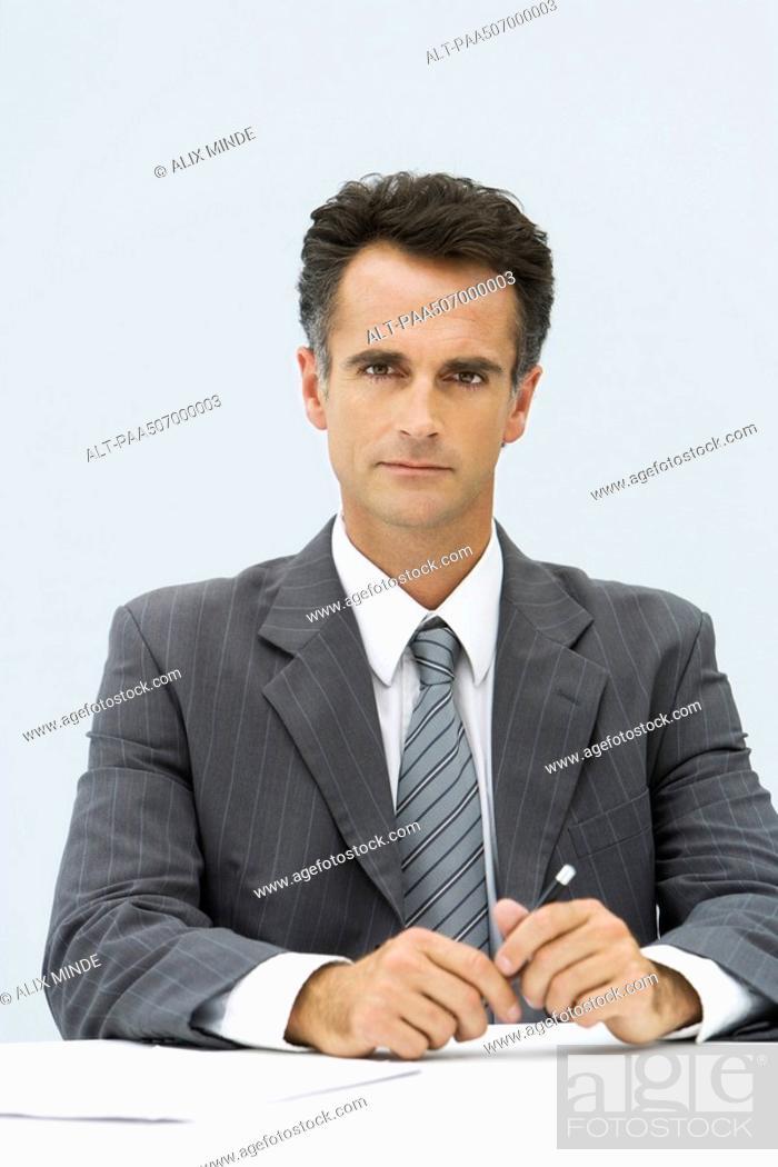 Stock Photo: Professional man looking at camera, holding pen.