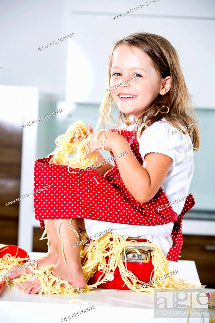Stock Photo: Germany, Girl playing with spaghetti on kitchen worktop.