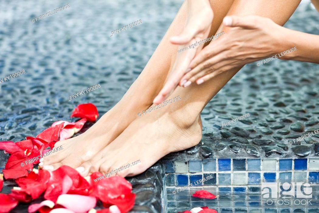 Stock Photo: Woman massaging her legs at the poolside.