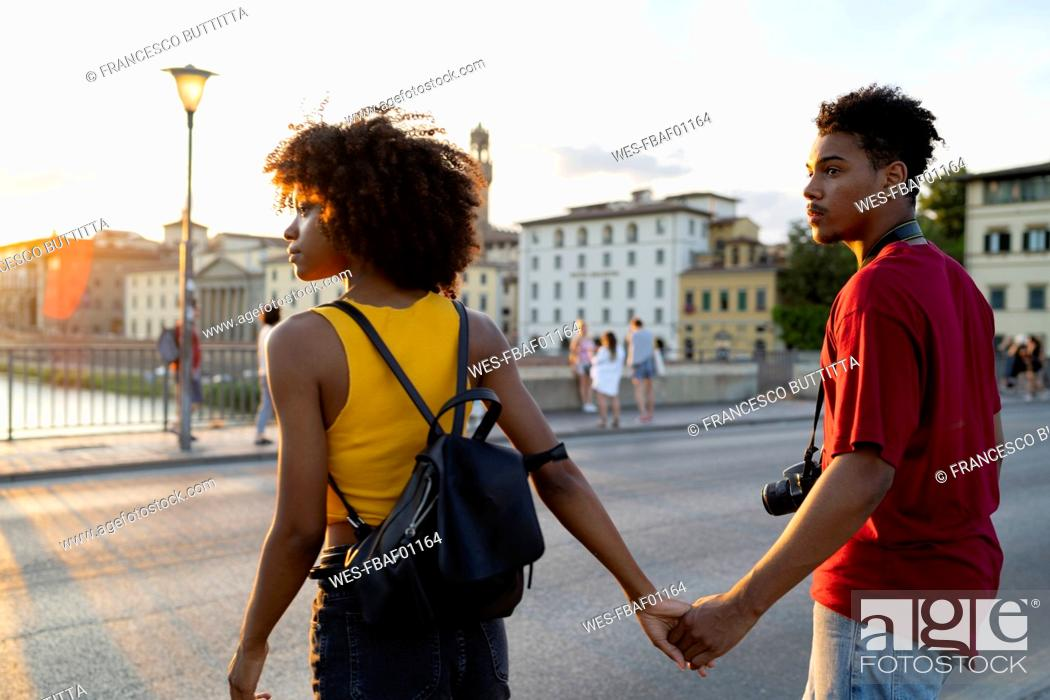 Stock Photo: Young tourist couple exploring the city at sunset, Florence, Italy.