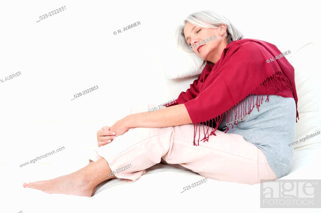 Stock Photo: Beautiful mature woman, wrapped in a red shawl, asleep on a sofa.