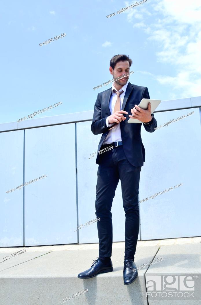 Stock Photo: Businessman using a tablet, standing, near a wall outdoors.
