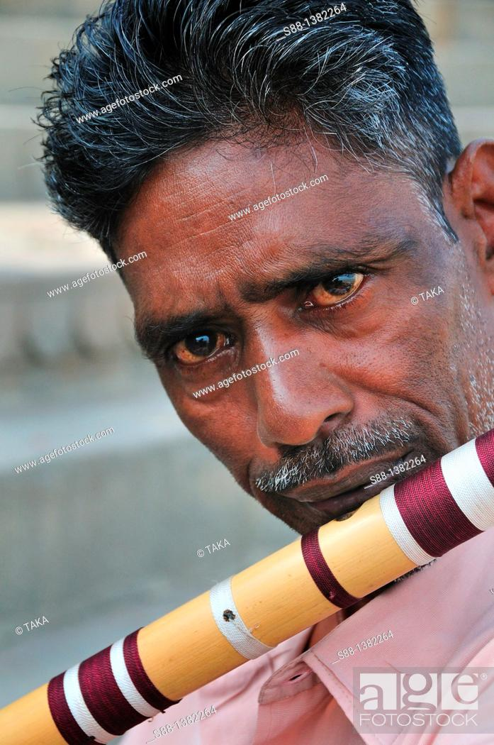 Stock Photo: Man who sells flute playing at the ghat by the Ganges river.