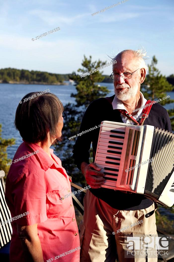 Imagen: Senior man playing accordion to senior woman.