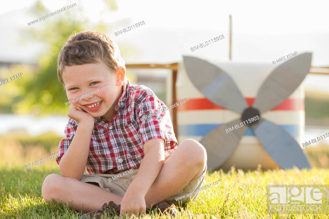 Stock Photo: Caucasian boy smiling in grass.