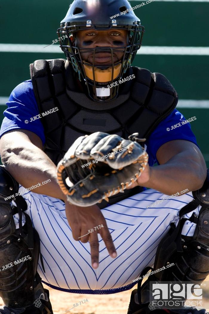 Stock Photo: Baseball catcher crouching on pitch, making secret signal with fingers, front view, portrait.