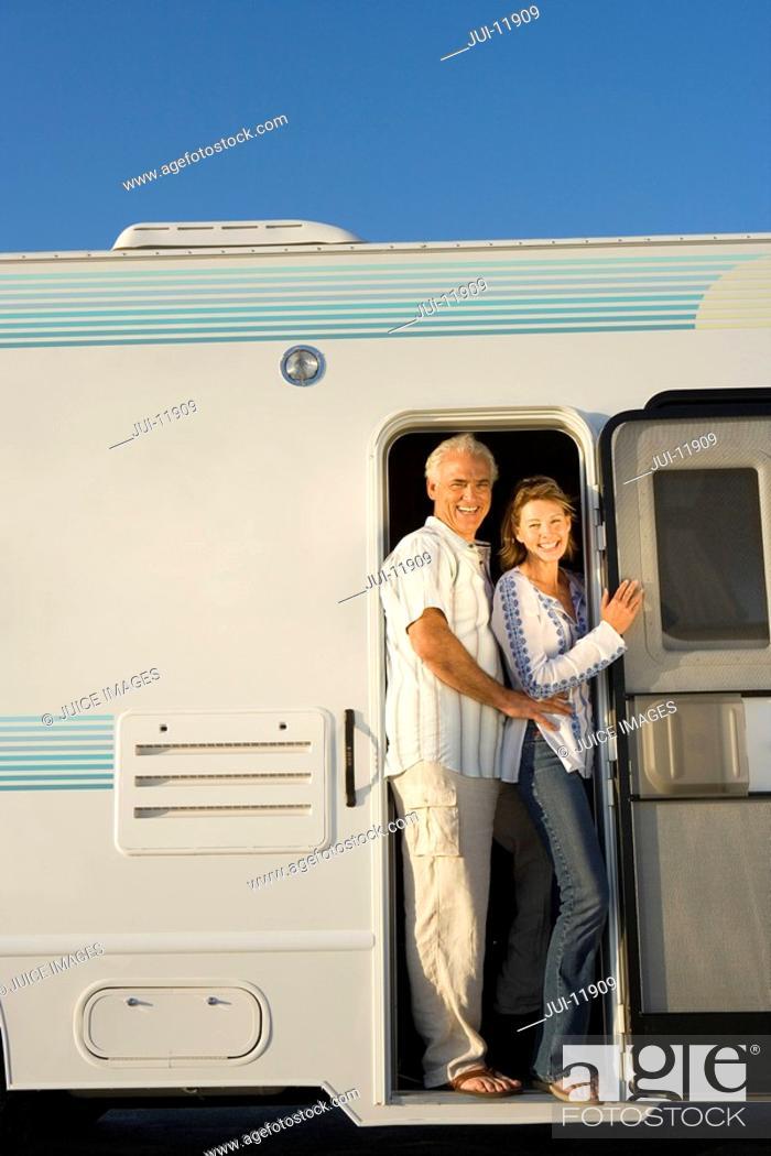 Stock Photo: Mature couple in door of motor home, smiling, portrait.