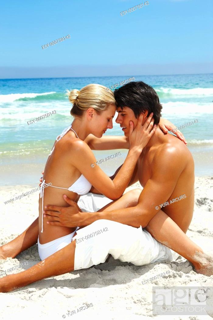 Stock Photo: Portrait of an affectionate young couple sitting together at the beach.