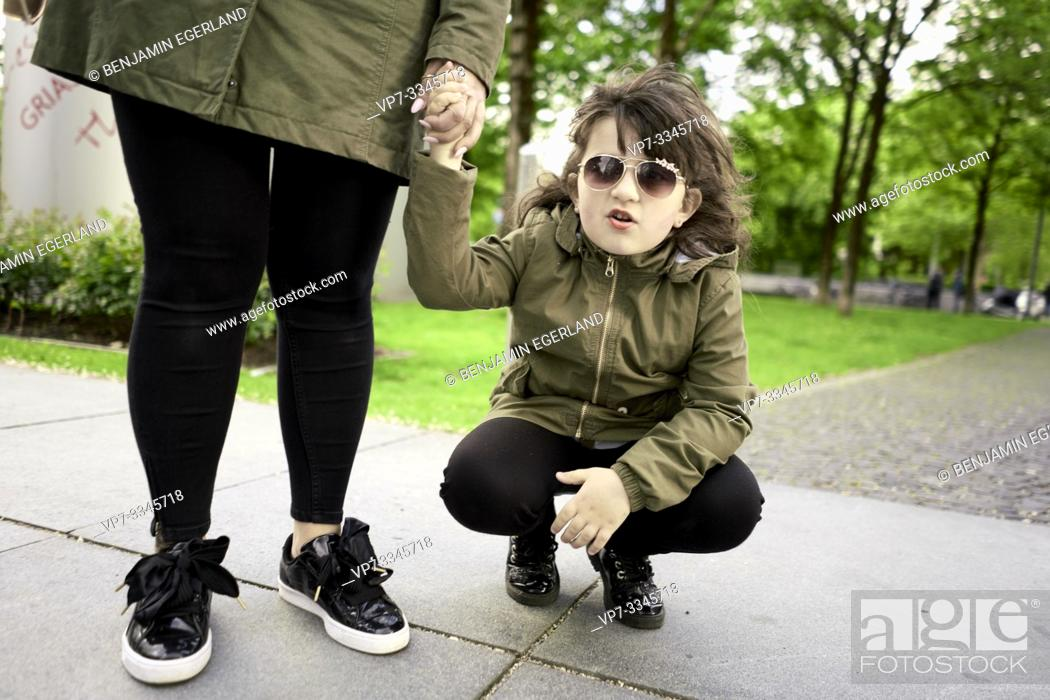 Stock Photo: daughter holding mother's hands in city.