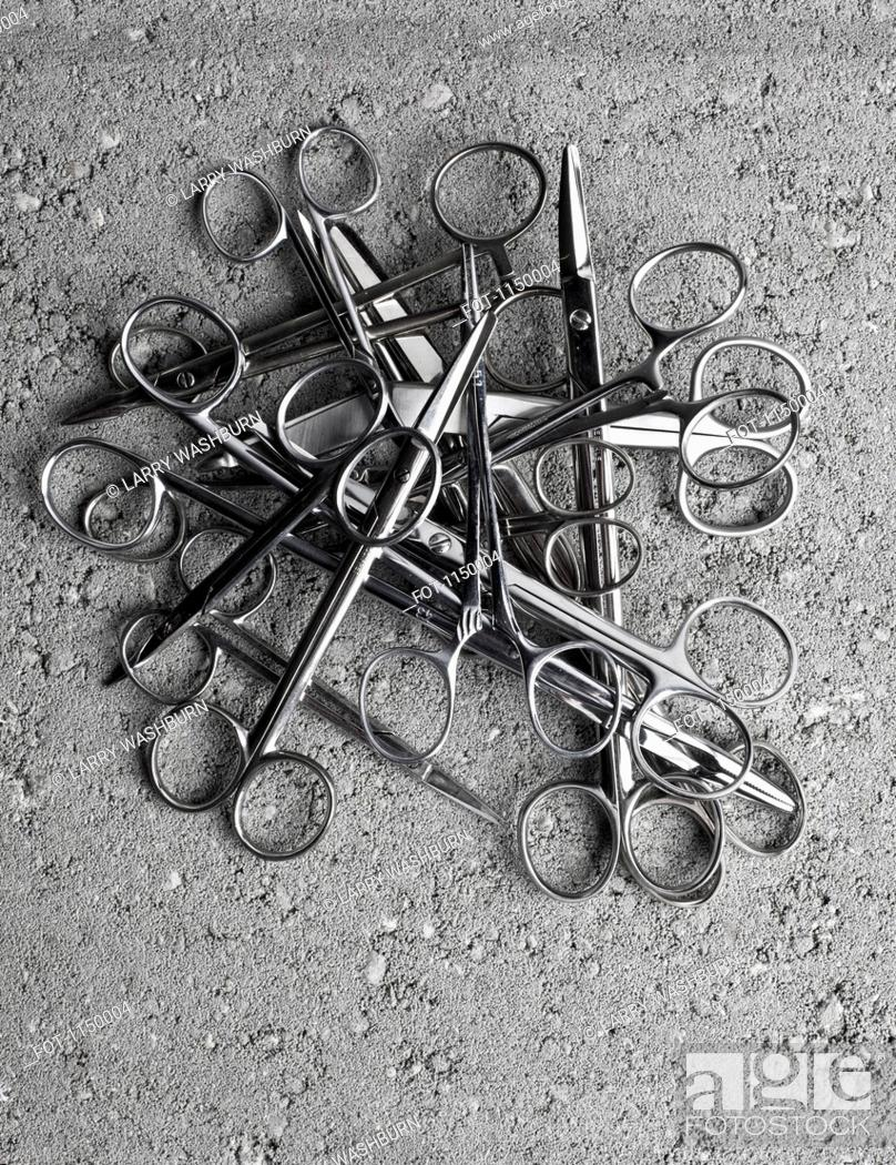 Stock Photo: A pile of surgical scissors on cement.