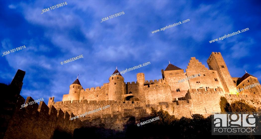 Stock Photo: France, Languedoc, Carcassonne, Castle walls illuminated at night.