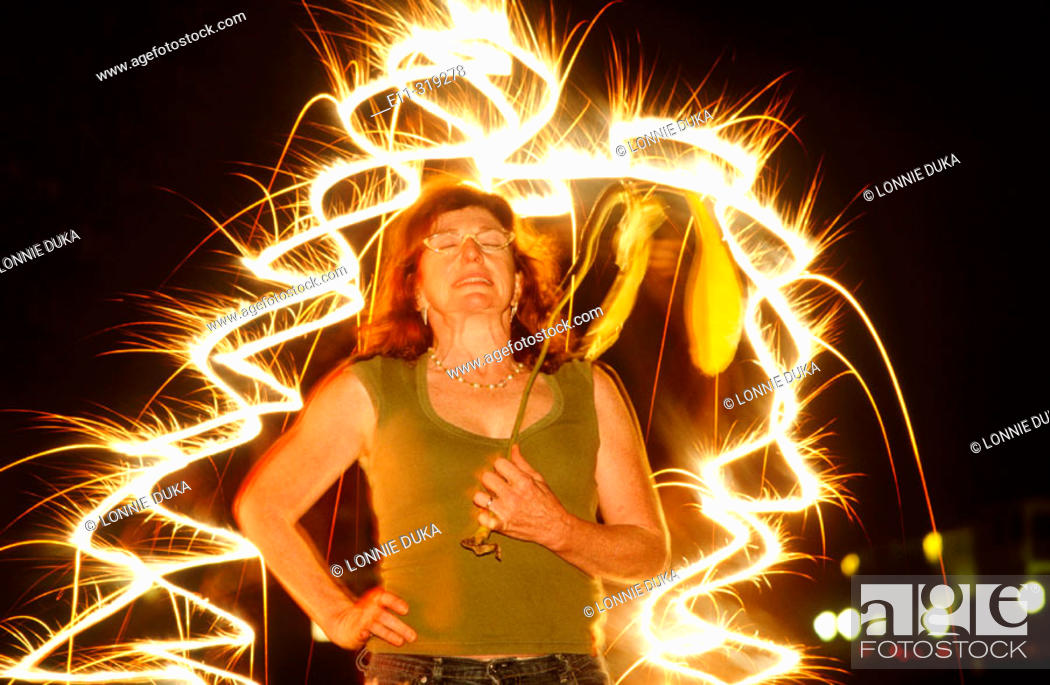 Stock Photo: Woman surrounded by sparkler fireworks.