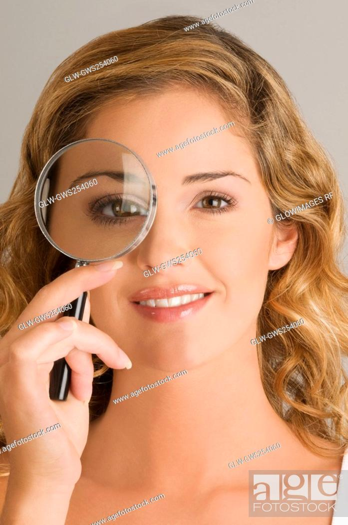 Stock Photo: Close-up of a young woman looking through a magnifying glass.