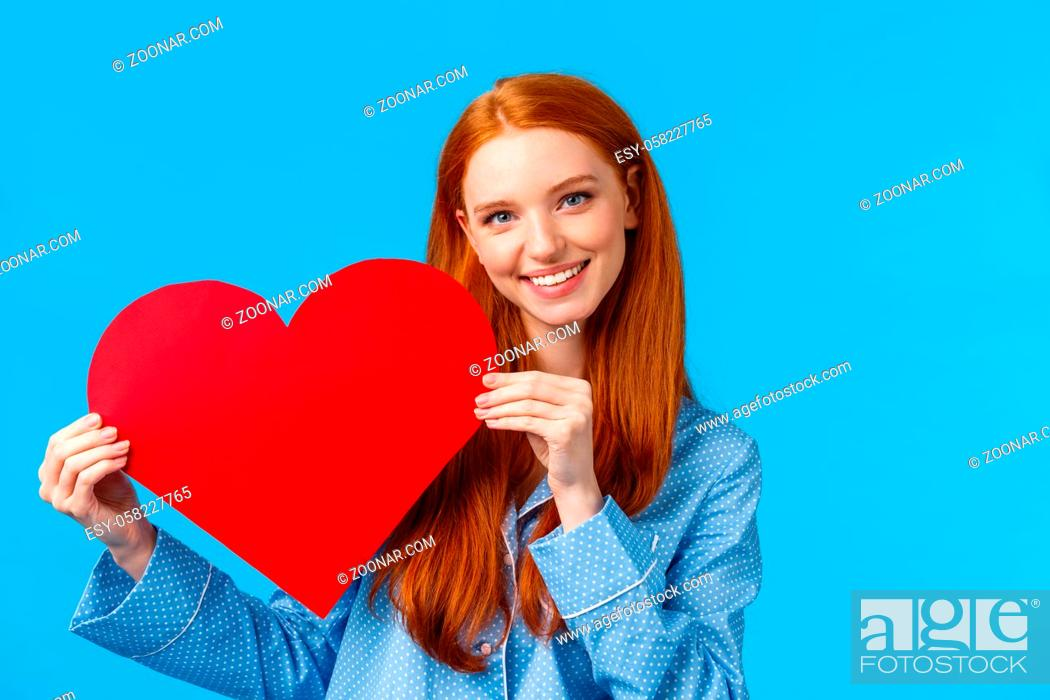Stock Photo: Tenderness, care and romance concept. Romantic good-looking redhead female in nightwear giving her affection and love, holding red heart sign and smiling.