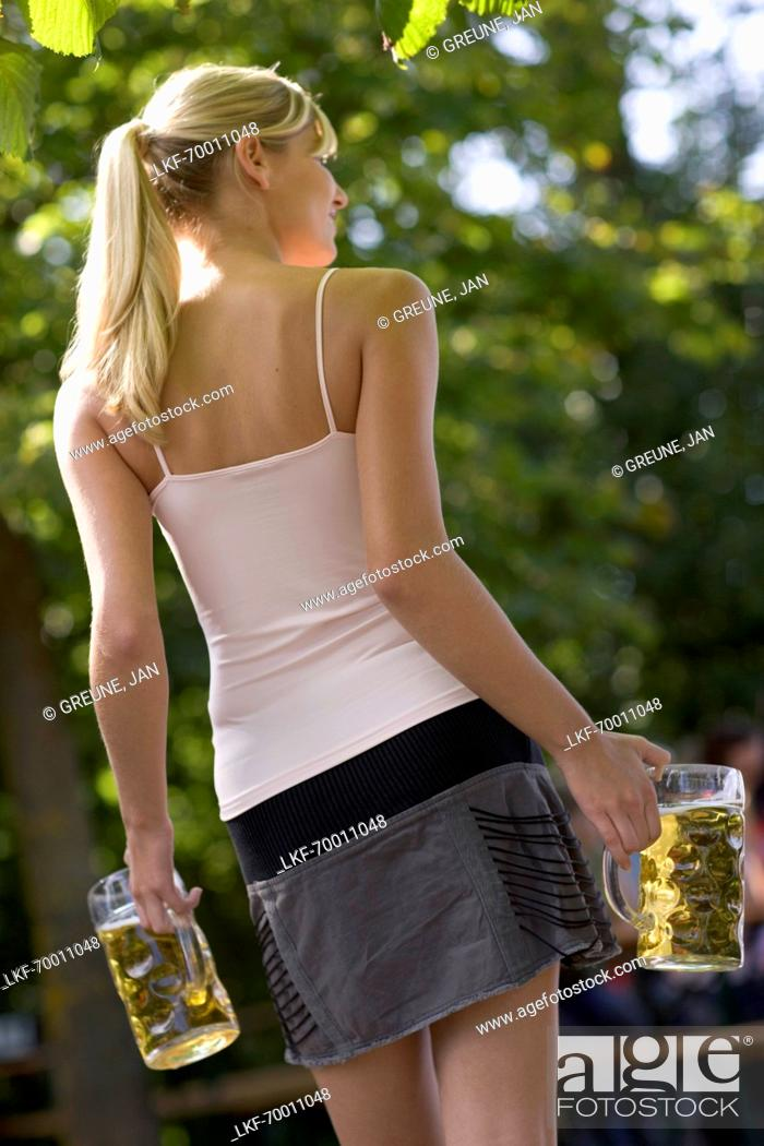 Young Woman In A Beer Garden Carrying Two Beer Steins Lake