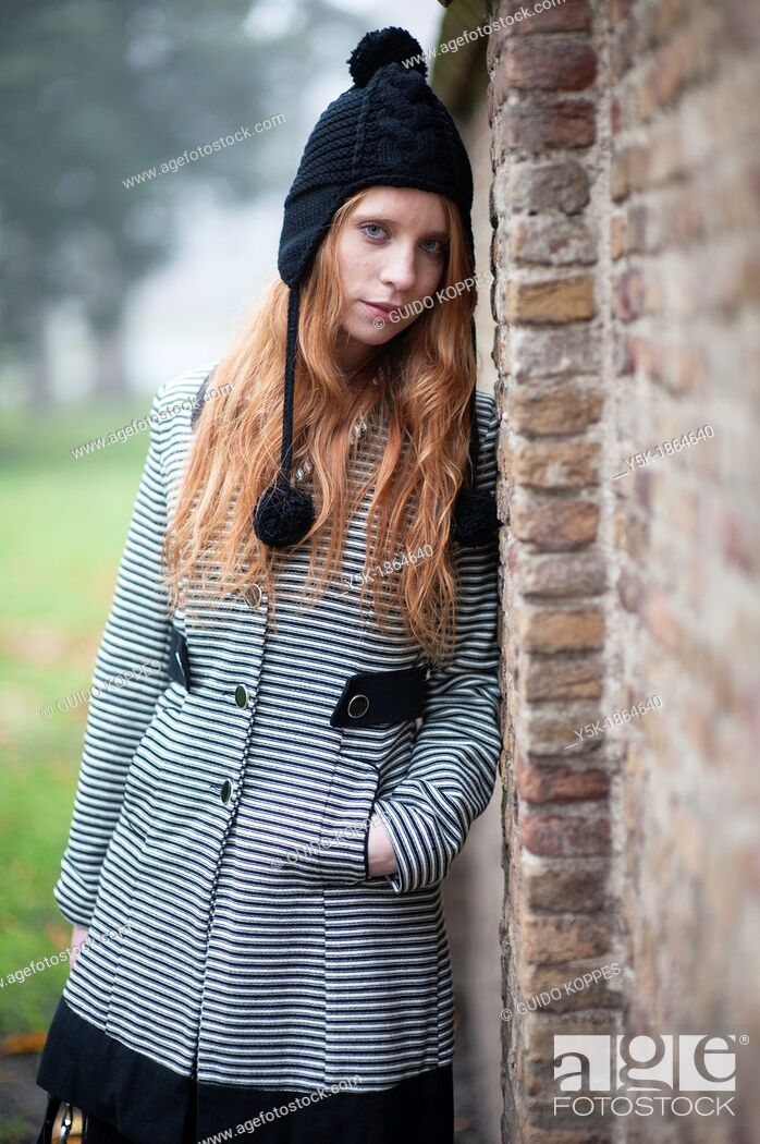 Stock Photo: Breda, Netherlands. Young, fashionable and redheaded woman in a city-park, leaning against a wall.
