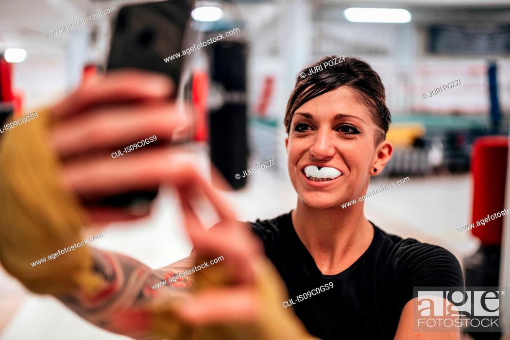 Stock Photo: Boxer taking selfie wearing gumshield in gym.