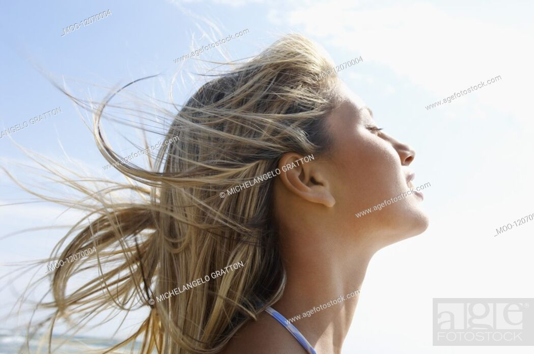 Stock Photo: Young woman on beach with wind-swept hair close up side view head shot.
