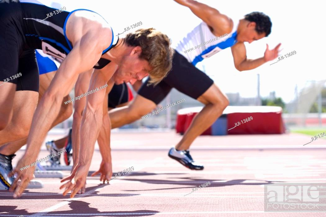 Stock Photo: Male sprinters on starting blocks, side view.