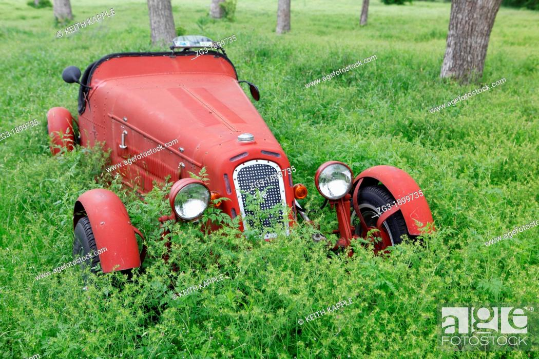 Stock Photo: Old Abandoned Rusty Vintage Convertible Car in a field of weeds out in West Texas.