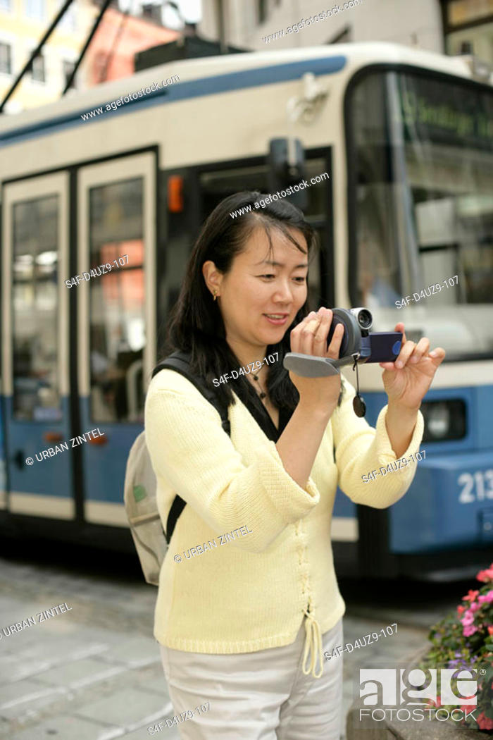 Stock Photo: Young Asian woman with a camera standing in front of a tramway, selective focus.
