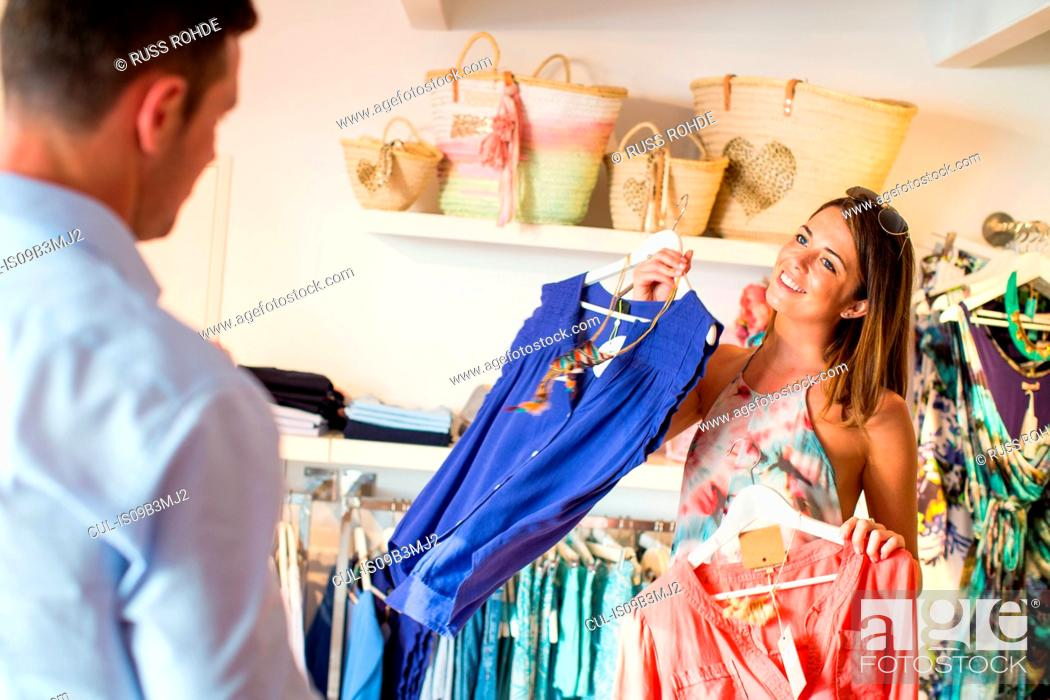 Stock Photo: Young woman tempting boyfriend to buy dress in boutique, Majorca, Spain.