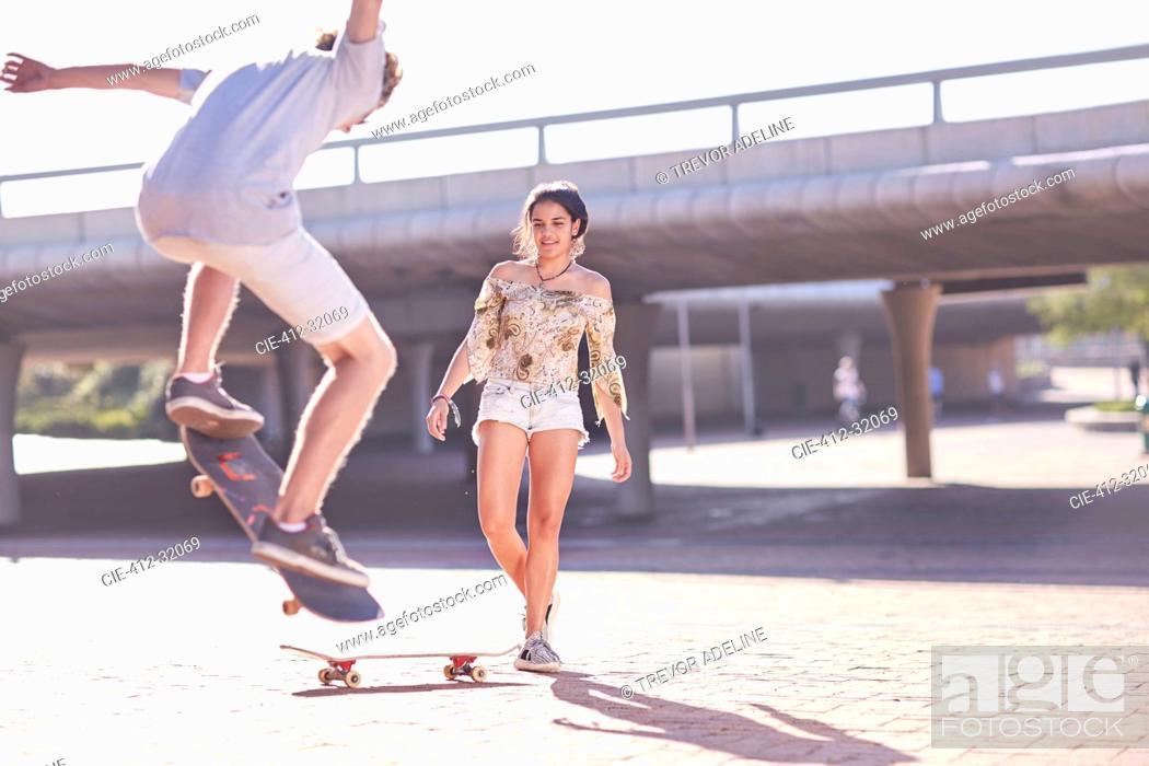Stock Photo: Teenage boy and girl skateboarding at sunny skate park.