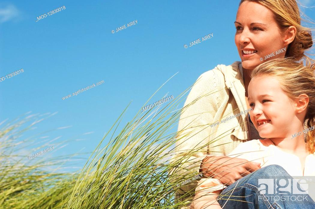Stock Photo: Happy mother and daughter sitting together in long grass against blue sky.