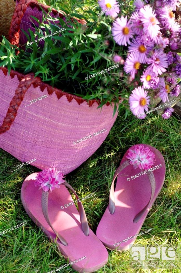 Stock Photo: Pink flip flops with a blossom and flowers.