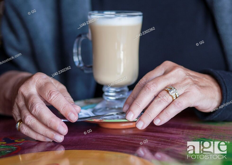 Stock Photo: Close up of Womans hands drinking capuchino.