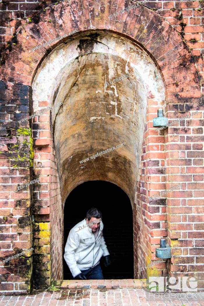 Stock Photo: Caucasian man with a white leather jacket and gloves in his 40's, 45's coming uo the stairs into a fort with a small arched entrance.