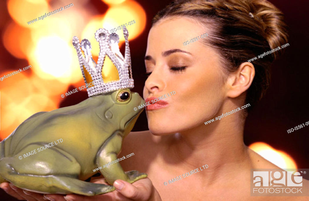 Stock Photo: Woman kissing toy frog.