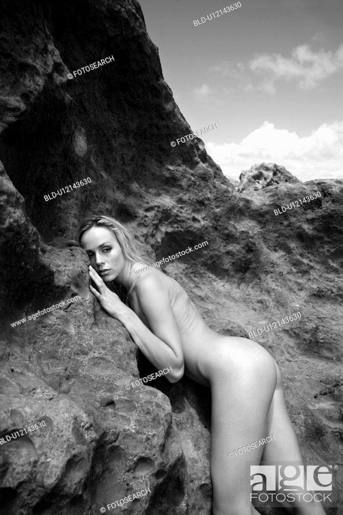 Stock Photo: Young adult nude Caucasian woman standing and leaning on rocks .